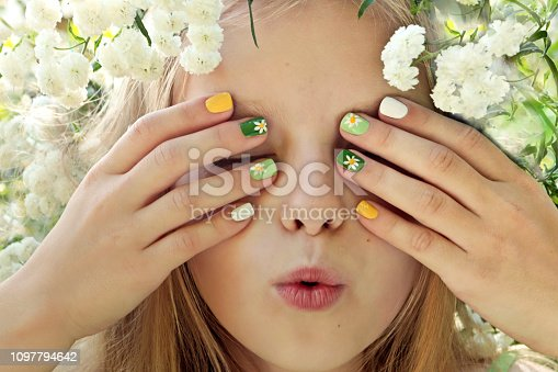 Children's multi-colored manicure on nails with a pattern of daisies on a little girl with blond hair.Hello, summer!Nail art.