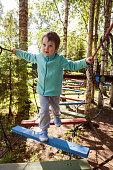 Children's obstacle course. Preschooler boy bravely walks the rope ladder