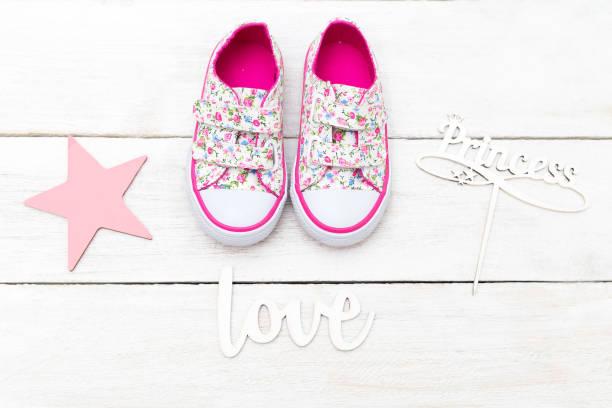 rosa kinderschuhe und inschriften auf einem weißen hintergrund aus holz. flach zu legen - barbiekleidung stock-fotos und bilder