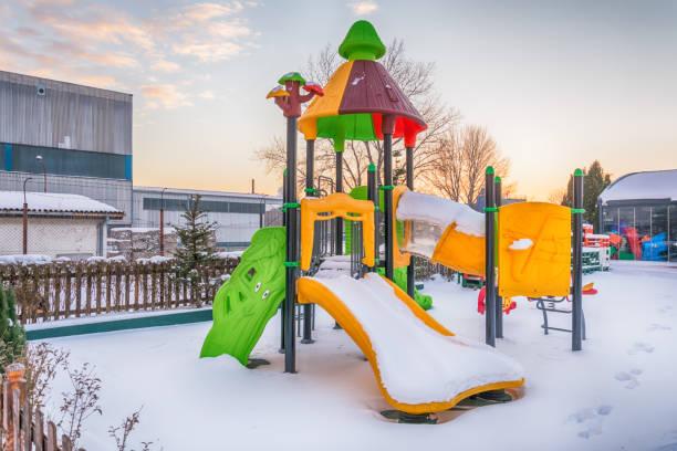 kinderspielplatz mit schnee bedeckt - spielplatz design stock-fotos und bilder