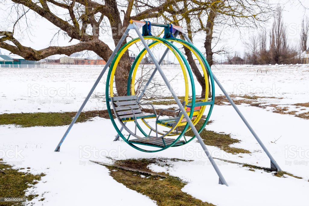 Children's playground in winter under snow. Swing, carousel and slide. Winter desolation stock photo