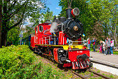 Kiev, Ukraine - May 9, 2015: Steam locomotive of old Toy Train can be seen in the station in Kyiv. Parents with children on the platform in the background.