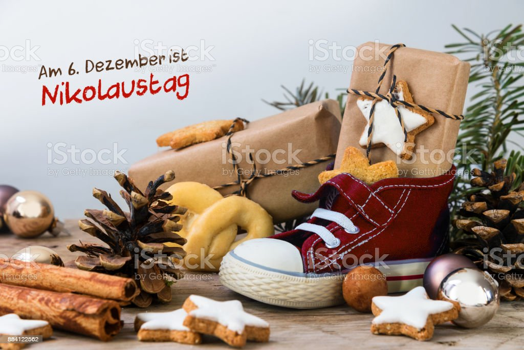 Children's shoe with sweets, gifts and christmas ornaments on rustic wood, german text Am 6. Dezember ist Nikolaustag, meaning  St. Nicholas Day December 6th stock photo