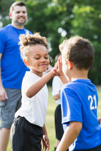 Children's soccer team, opponents giving high-fives stock photo