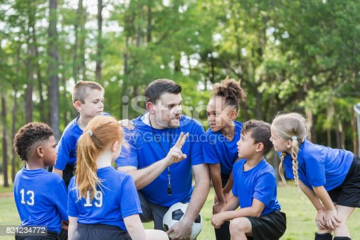 Six multi-ethnic children 6-7 years old playing soccer at summer camp. They are gathered around their coach who is talking strategy.