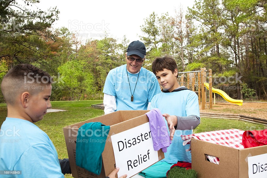 Sports team of children and coach collecting food, clothing and...
