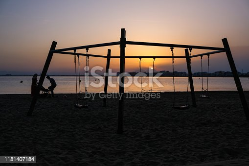 Children's swing on the beach on a background of sunset and sea. Silhouettes of a family of two parents and a child. Concept of family vacation. Summer sunset in Spain, Catalunya. Playground on beach.