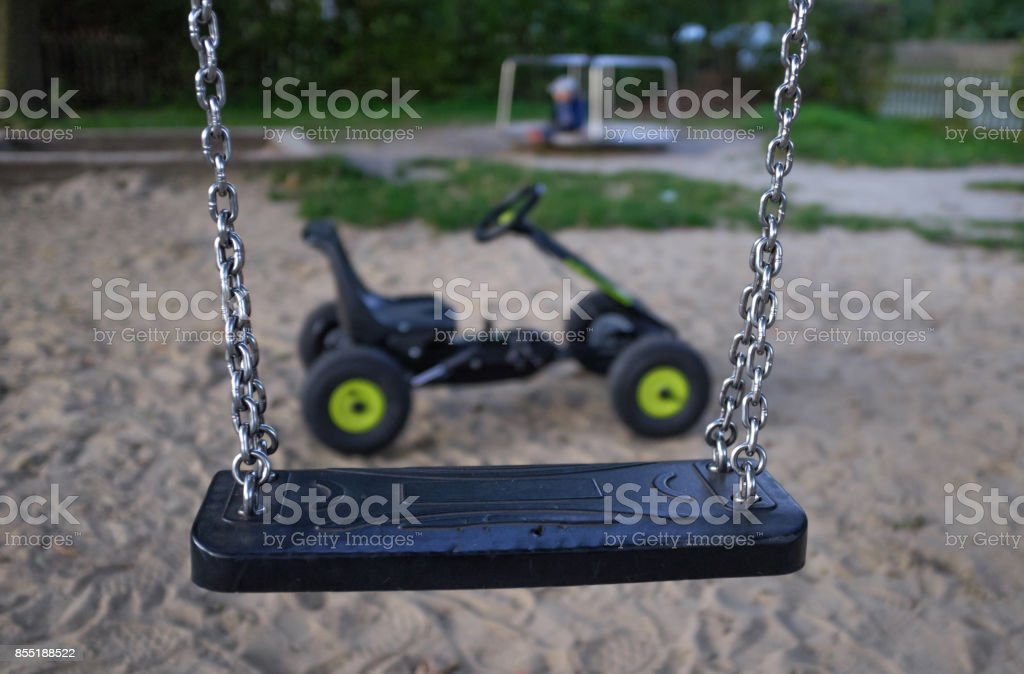 A children's swing with a playground in the background stock photo