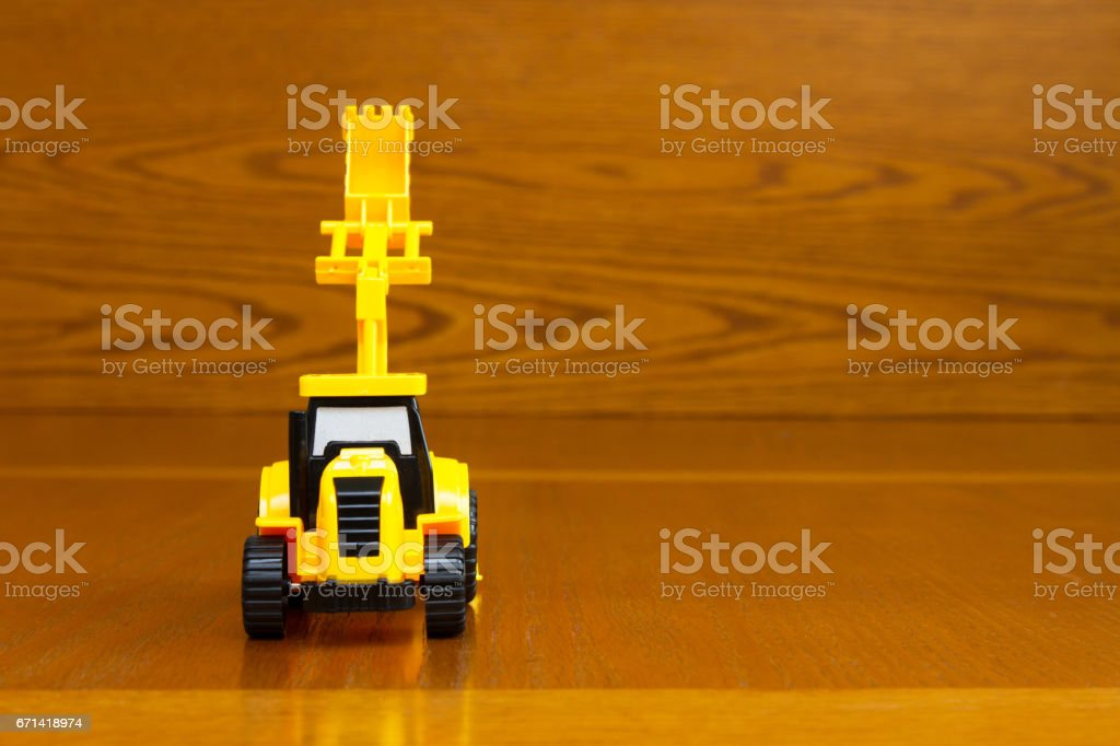 Children's tractor yellow with a raised bucket on a brown background stock photo