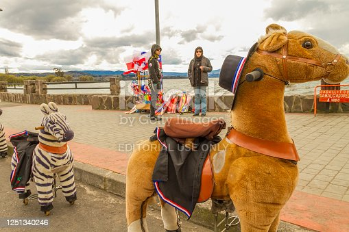 September 18, 2019 - Villarrica, Chile: Riverside view with a group of larges typical chilean childrens wheeled toy horses dressed with the national attire and classic chupalla hat for rent in front of Villarrica Lake in Southern Chilean Patagonian with a typical rural street view in the National Country Day, September 18th (18 de Septiembre).  Villarica village town is located in southern zone in Chile, in the lakes zone area, the town is very famous for his volcano and lake, is situated near to Calafate, Bariloche Argentina and Torres del Paine National Park, Chile, South America.