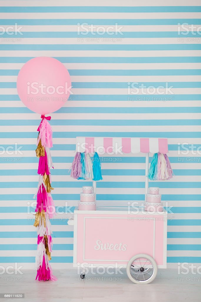 Children's zone with sweets: lollipops, ice cream, macarons, balloon and candy bar. Children room with blue stripe background stock photo