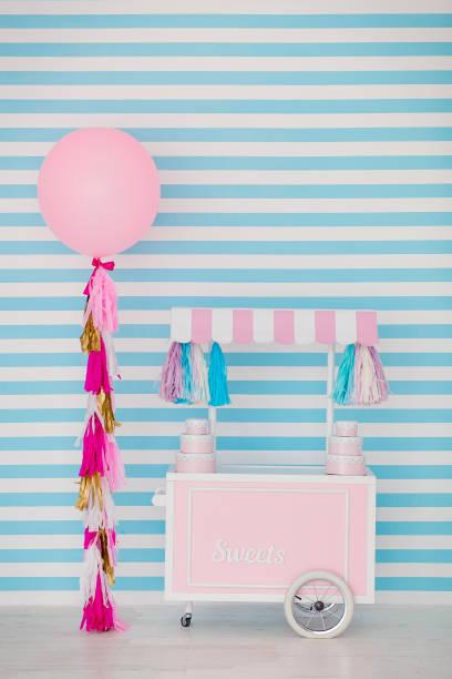 kinderbereich mit süßigkeiten: lutscher, eis, macarons, ballon und candy bar. kinderzimmer mit blauen streifen hintergrund - eis ballons stock-fotos und bilder