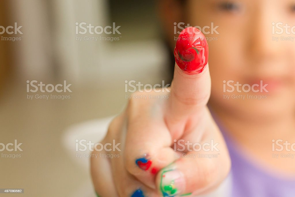 childrent painting red color on her finger stock photo