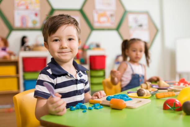 kinder spielen mit ton spielen im klassenzimmer. - knete spiele stock-fotos und bilder