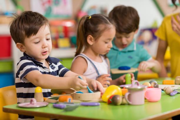 kinder spielen mit ton spielen im klassenzimmer. - 2 3 jahre stock-fotos und bilder