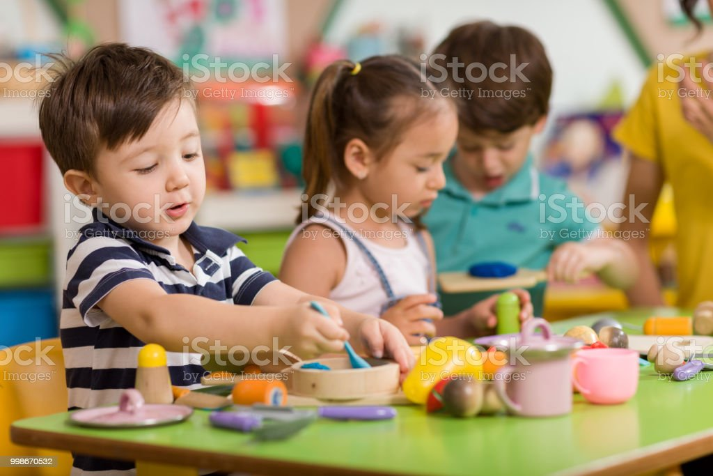 Childs are playing with play clay in classroom. stock photo