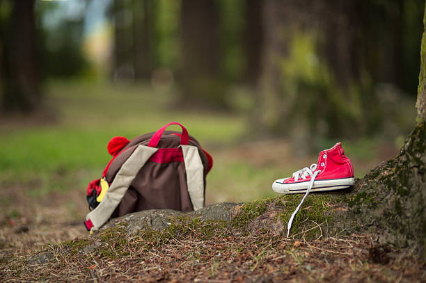 child's backpack and shoe left behind in a wooded park - criança perdida imagens e fotografias de stock