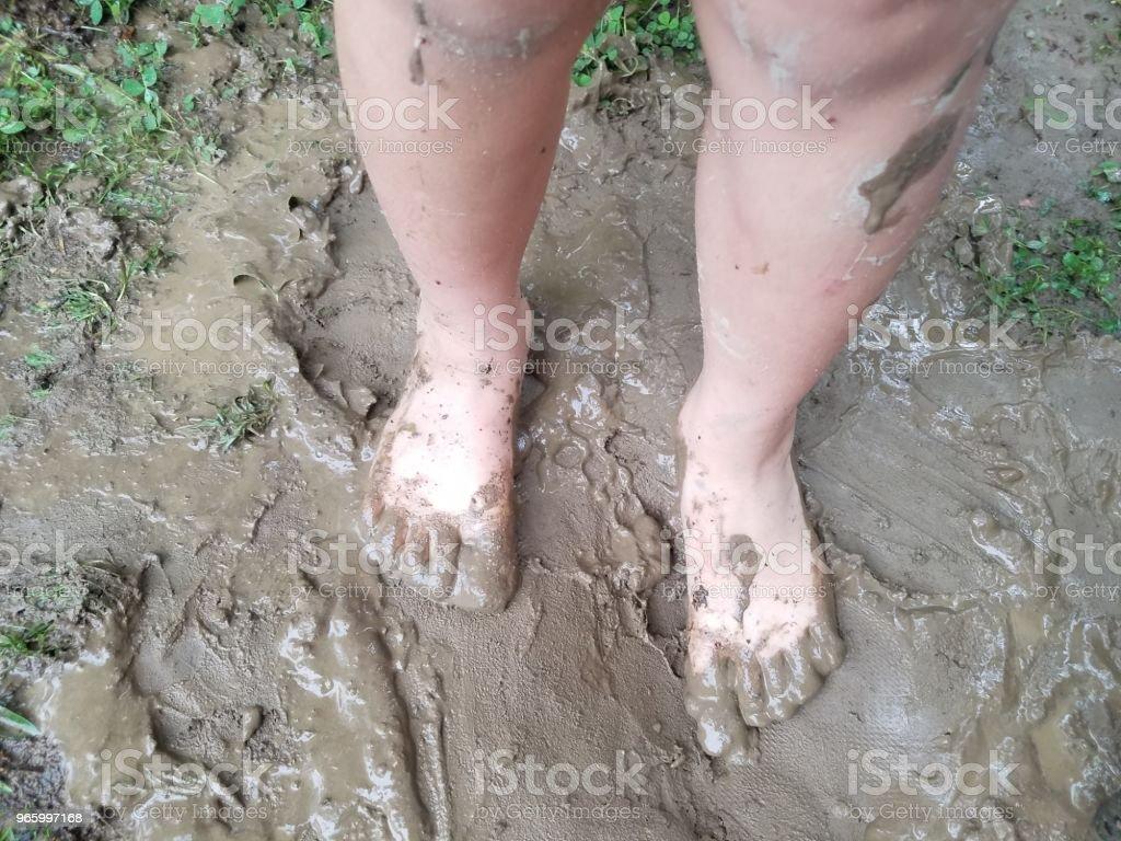 child's bare feet in mud – zdjęcie