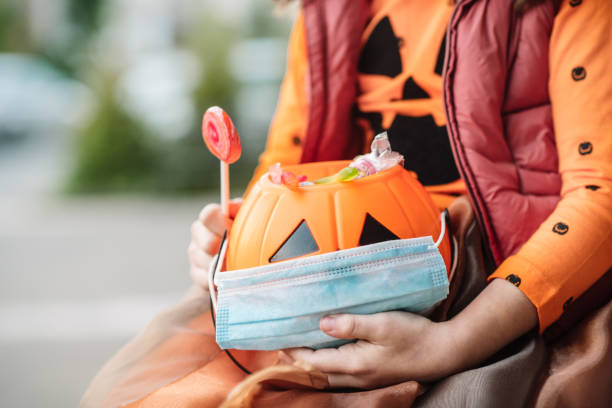 Child's basket with sweets and protective face mask on Halloween in autumn Little girl trick or treating during COVID-19 pandemic. halloween covid stock pictures, royalty-free photos & images