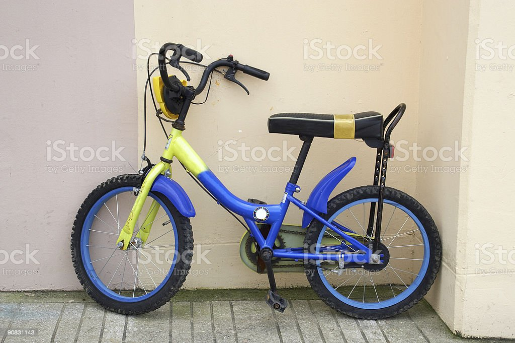 Child's bike leaning parked on a wall. royalty-free stock photo