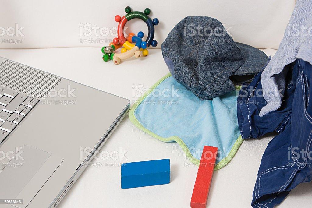 Um childs roupas brinquedos e um computador portátil foto de stock royalty-free