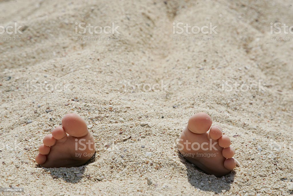 Child's feet in the sand close-up stock photo