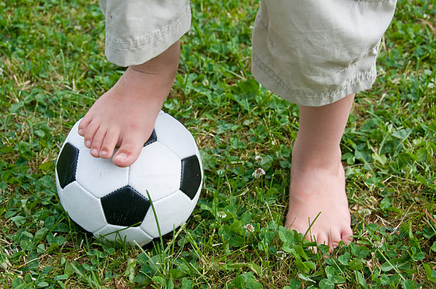 Child's Feet on a Football stock photo
