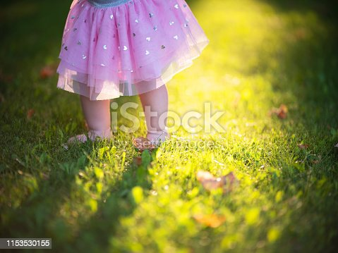 Child's feet on the green grass with sun light