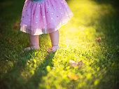 Child's feet on the green grass with sun light