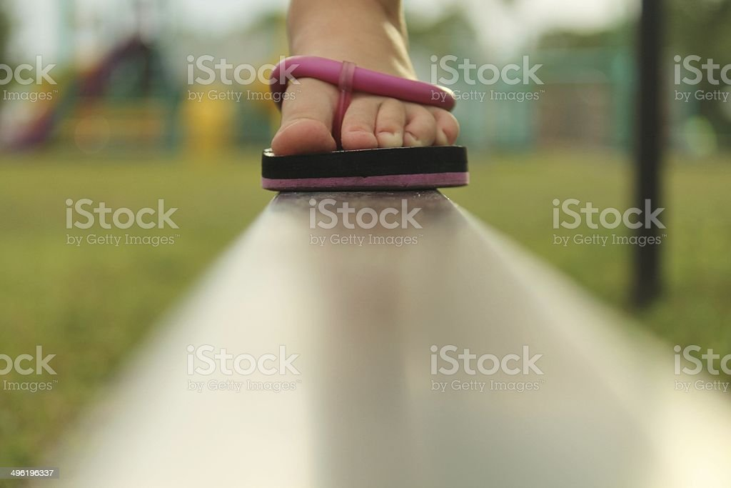 Child's foot on a balance beam stock photo