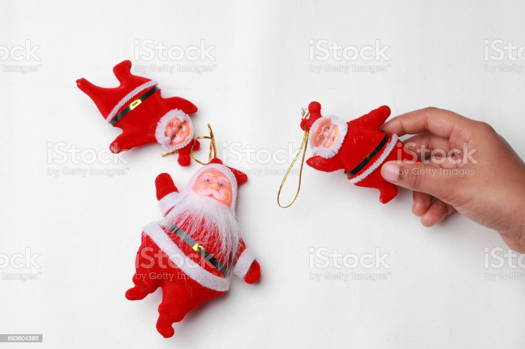 A child's hand arranges Santa dolls on a white background stock photo