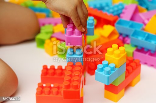 istock Child's hand building plastic toy blocks with blurred background 840783710