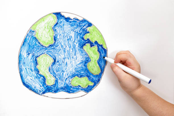 Child's hand drawing planet Earth with a marker Child's hand drawing planet Earth with a marker. Close up. cartoon and kids stock pictures, royalty-free photos & images