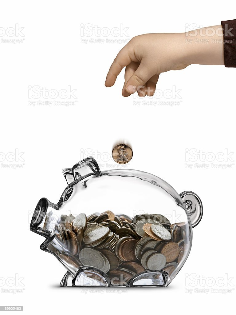 Childs Hand Dropping Coin Into Half-filled Clear Piggy Bank royalty-free stock photo