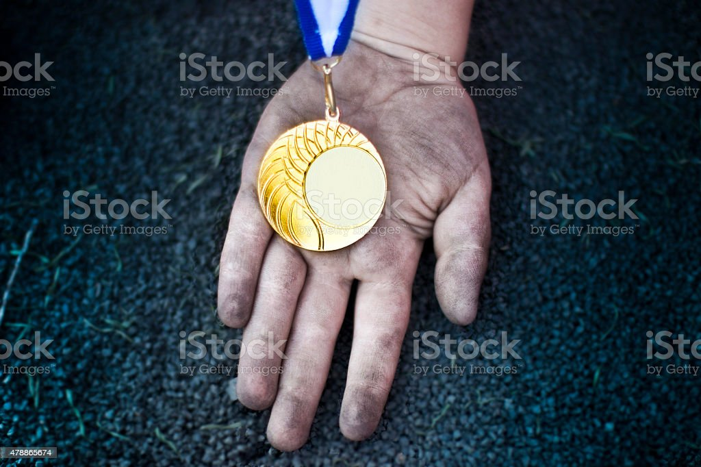 Child's hand holding a gold medal. Space for text stock photo