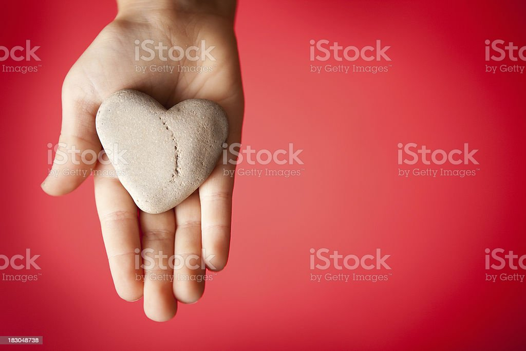 Child's Hand Holding a Heart-Shaped Rock on Red Background royalty-free stock photo