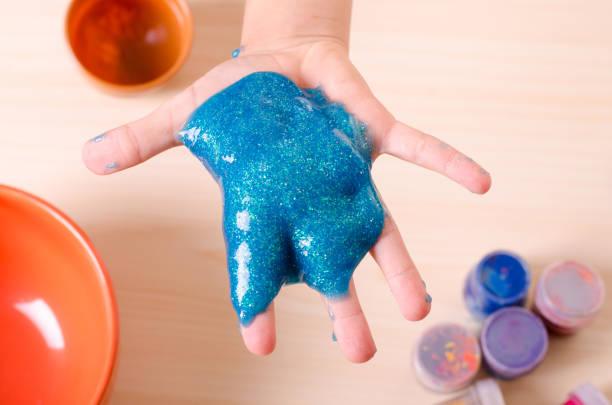child's hand holding bright glitter slime. kid playing with slime, worldwide popular self made toy. - bagno zdjęcia i obrazy z banku zdjęć