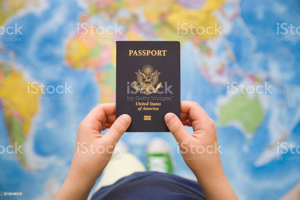 Child's hand holding US passport. Map background. Ready for traveling. Open world. stock photo