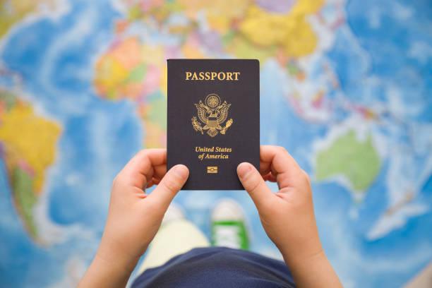 Mano infantil pasaporte de Estados Unidos. Mapa de fondo. Listo para viajar. Mundo abierto. - foto de stock