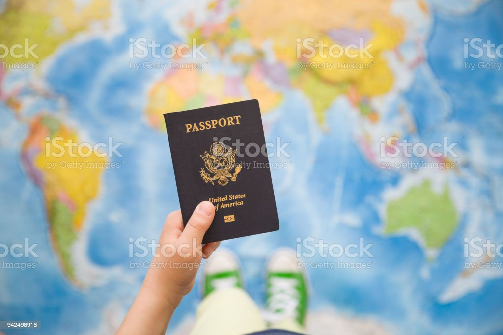 Child\'s hand holding US passport. Map background. Ready for...