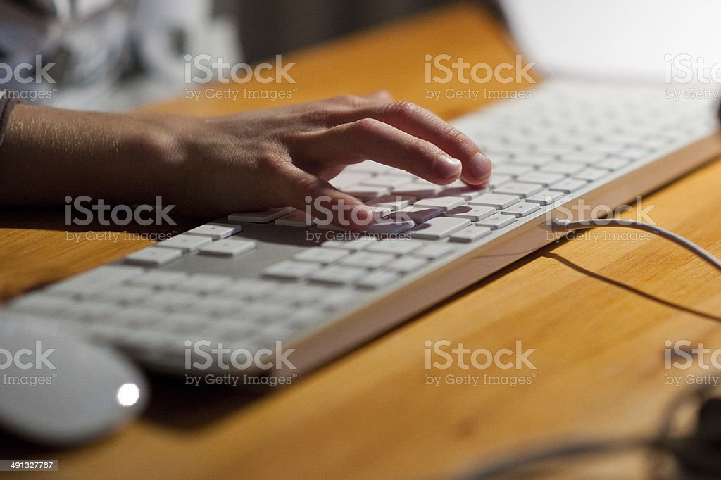 Child's hand on a computer keyboard stock photo
