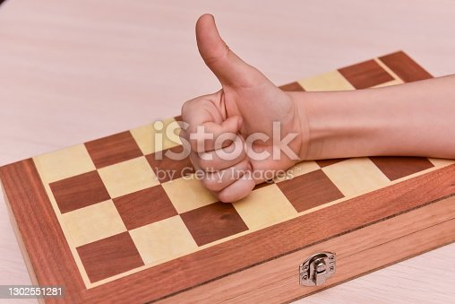 child's hand on the chessboard showing thumb up. cool game at home.