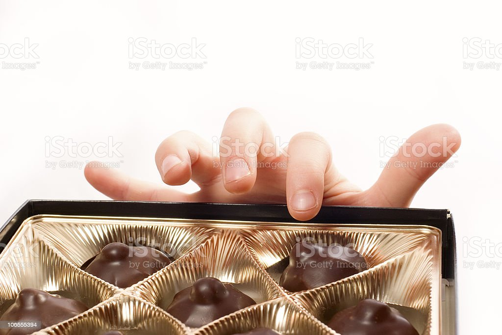 Child's hand picking chocolate candy from box isolated over white royalty-free stock photo