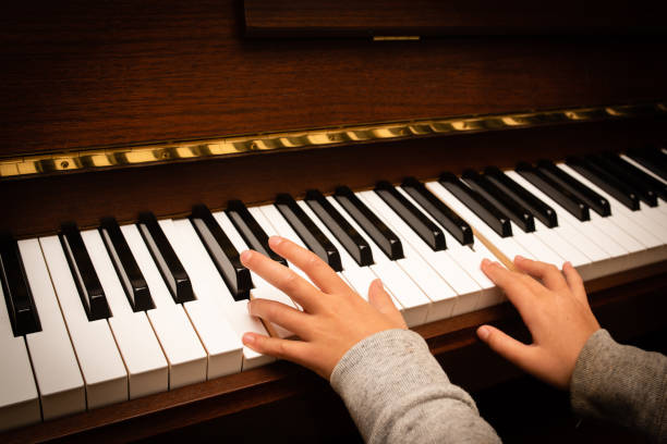 Child's hand playing the piano stock photo