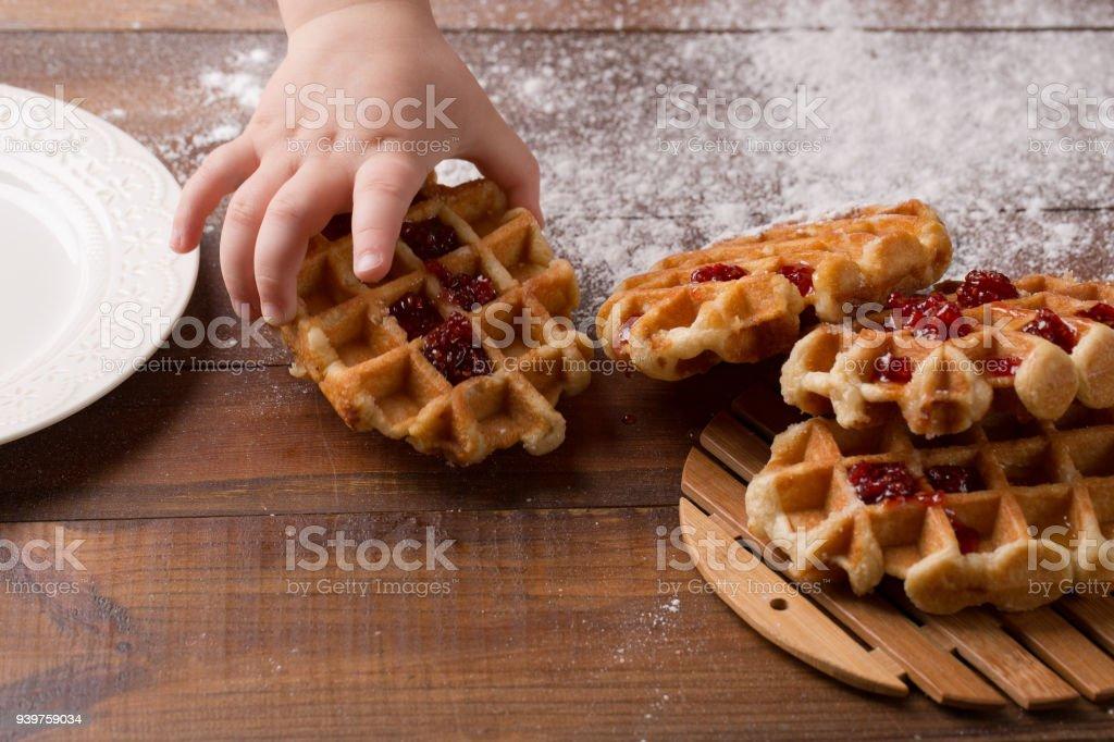 main de l'enfant prend savoureuses gaufres faites maison et confiture de fraises - Photo