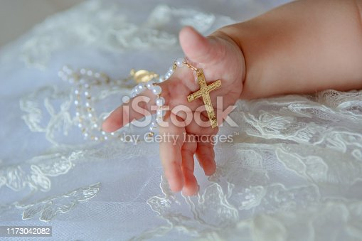 Child's hand with a crucifix on a white cloth.