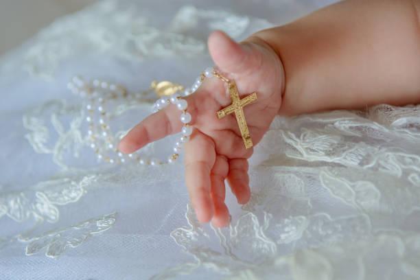 kinderhand mit einem kruzifix auf einem weißen stoffhintergrund. - taufe texte stock-fotos und bilder