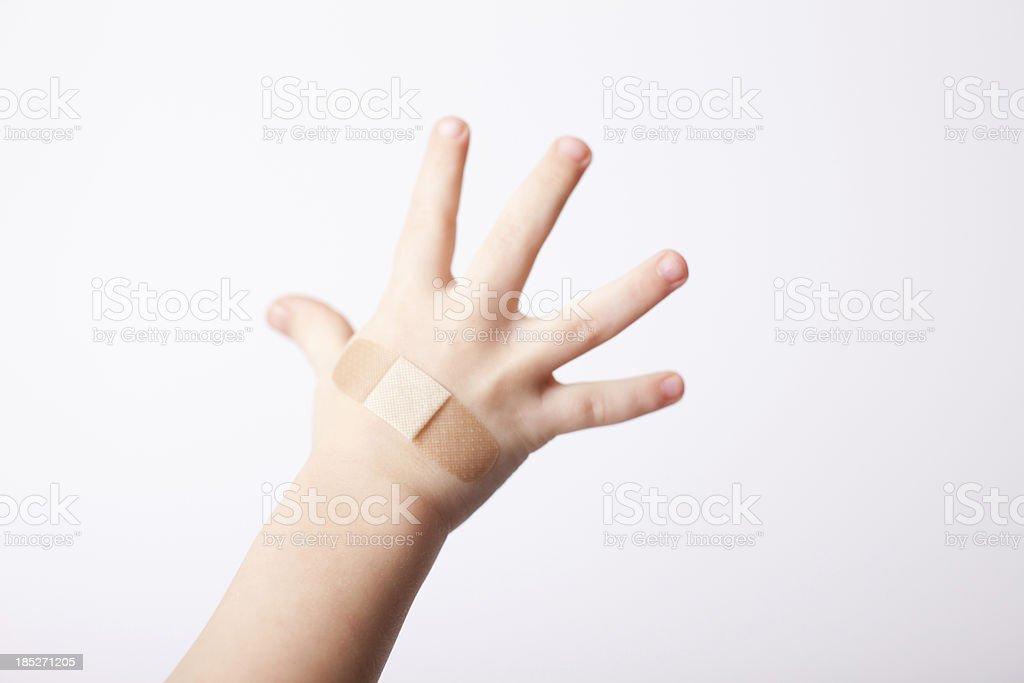Child's Hand With Bandage Applied, Isolated on White stock photo