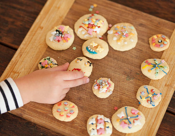 Child's hand with brightly decorated biscuits stock photo