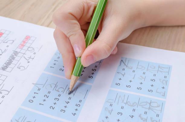 Kinderhand mit falschem Bleistift, Heimatwortk, Mathematik – Foto